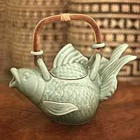 """Stoneware teapot, 'Green Fish Legend' £60.77 5.7"""" H x 9.3"""" W x 6.3"""" D   20.0 oz. 1.00 kgs   A fantastic fish, this design is composed by the organic imagination of Tat Yan Soo. The artisan molds the teapot from select clay, delicately shaping fluid fins and scales. The novel teapot features a rattan handle.    An artisan story card will be included with your purchase."""