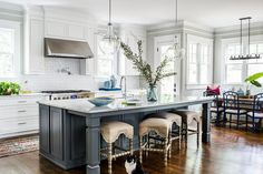 Four beige burlap abacus stools sit at a charcoal gray island topped with a white and gray marble countertop fitted with a sink and lit by Kichler Pendants.