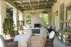 A large covered porch out back has a stone fireplace and is furnished with French antiques and accents. Outdoor Living Rooms, Outside Living, Porches, Built In Braai, Outdoor Furniture Sets, Outdoor Decor, Adirondack Furniture, Rustic Outdoor, Outdoor Dining