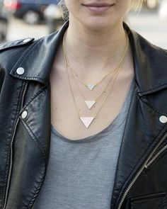 Black jacket with a three tiered gold necklace, gray tee