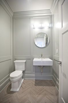 Chic powder room with paneled gray green walls with matching gray green crown moldings and gray green base boards. Powder room with round mirror over floating sink next to toilet over herringbone floor. Half Bathroom Decor, Small Bathroom, Bathroom Images, Bathroom Paneling, Eclectic Bathroom, Concrete Bathroom, White Bathrooms, Luxury Bathrooms, Master Bathrooms