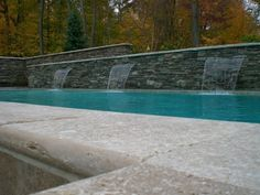 3 sheer jet waterfalls among a wall of natural stone veneers. By Signature Outdoor Concepts
