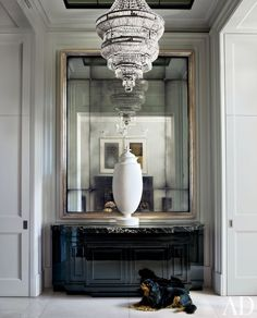 A 1940s plaster urn graces the entrance hall of a London townhouse. Archie, the homeowners' Cavalier King Charles spaniel, rests on the floor.  ARCHITECT: Jan Swanepoel DESIGNER: Hubert Zandberg PHOTOGRAPHER: Simon Upton
