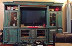 Refinished an oak entertainment center with teal paint, then sanded it down to give it a vintage look.