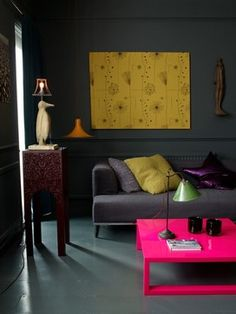 Abigail Ahern interiors eclectic-living-room This electric-pink table, along with the bright yellow artwork, pops and helps to define the room, which could have been a bit of a black hole without such an energizing color.
