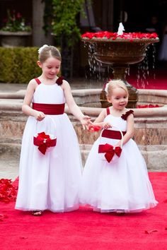 Flower girls with white tool dresses and red rose petals walking down the red carpet before the outdoor wedding ceremony Red Bridesmaids, Burgundy Bridesmaid Dresses, Frocks For Girls, Girls Dresses, Princess Flower Girl Dresses, Flower Girls, Girls First Communion Dresses, Kids Gown, Maid Of Honour Dresses