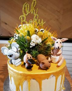 Australiana themed baby shower cake featuring Australian Native Wildflowers and Australian Animals. Cake Toppers made with fondant. Semi naked gold drip cake.