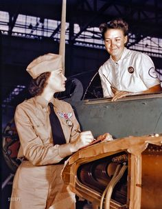 """August 1942. """"Formerly a sociology major at the University of Southern California, Mrs. Eloise J. Ellis (left) now """"keeps 'em flyin'"""" at the Naval Air Base, Corpus Christi, Texas. She is a supervisor under civil service in the Assembly and Repair Department. It is her job to maintain morale among the women by helping them solve housing and other personal problems. With her is Jo Ann Whittington, an NYA trainee at the plant."""""""