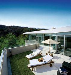 moderne terrassengestaltung liegesessel sonnenschirm grüner rasen