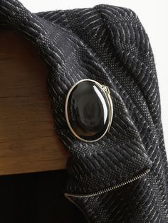 Gesine Hackenberg - black locket with springform latch brooch, urushi lacquer on textile, silver, steel needle