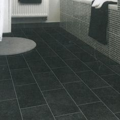 Complete your home with this stone effect dark tiled vinyl flooring. With a base color of black, complemented with u8ndertones of grey speckles, this vinyl would go well in any bathroom or kitchen. Retailed with a total thickness of 2.0mm and a wear layer of 0.20mm this vinyl has very good resilience and strength. Vinyl Flooring Uk, Stone Flooring, Natural Stones, Tile Floor, Living Spaces, Strength, Base, Bathroom, Grey