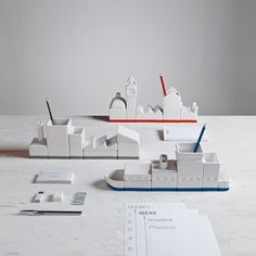 Modular desk containers shaped like a city, a ship, and a factory. Definitely a cool, different way to decorate your office.