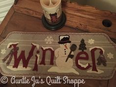 """Auntie Ju's Quilt Shoppe  - Frosty's Winter Runner kit, $37.99 Runner finishes approx. 10 x 27.5"""" - kit includes pattern, wool, backing and buttons.  Floss is not included (http://stores.auntiejusquiltshoppe.com/frostys-winter-runner-kit/)"""