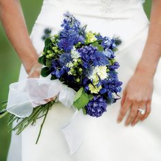 Cody held a natural, loosely tied bouquet of blue delphiniums, thistle, Queen Anne's lace, and hypericum berries, designed to look as if she'd gathered the flowers in the meadow where she was married.