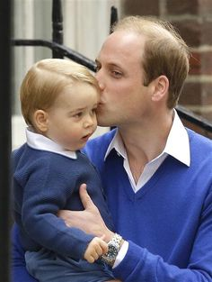 Prince William kisses Prince George of Cambridge as they arrive at the Lindo Wing after Duchess Kate gave birth to a baby girl at St Mary's Hospital in London on May 2, 2015.