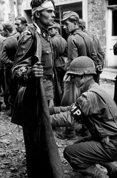 A US MP of the 2nd Armored Division with a SS soldier of Panzergrenadier Division Götz von Berlichingen, Caen, Normandy, France 1944. (Photo by Robert Capa)