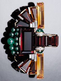 CITRINE, EMERALD AND DIAMOND BROOCHPENDANT, CIRCA 1930. Of geometric design set with radiating lines of step-cut citrine, embellished with emerald beads and points, highlighted with baguette and single-cut diamond detail.