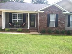 Red brick and gray siding, ranch house. White trim, black shutters
