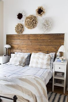 Bedroom decorations in neutral colors with a reclaimed wood headboard and a collection of homemade African feather Juju hats/wreaths. via www.songbirdblog.com