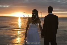 AUSTRALIA, QUEENSLAND, FRASER ISLAND. A COUPLE HAND IN HAND WATCH THE SUN SET from the beach at Kingfisher Bay on Fraser Island.  AUSTRALIA, Queensland, Fraser Island  A couple hand in hand watch the sun set from the beach at Kingfisher Bay on Fr. Image from Discover Images.com.