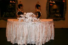 Overflowing sweetheart table arrangement with white Phalaenopsis orchids and willow