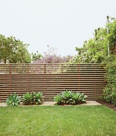 A once-sloping yard behind a remodeled house in San Francisco's Bernal Hill neighborhood now has a slatted fence, climbing vines, and fox...