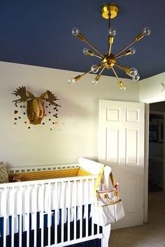 whimsical woodland nursery for a little boy | eclectic navy blue, yellow (mustard) and red-orange nursery | vintage sputnik light | crib bedding