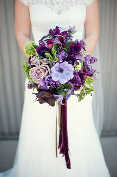 Purple Wedding Inspiration: A dramatic mix of wild purple flowers and greenery is tied with sophisticated strands of velvet ribbon.