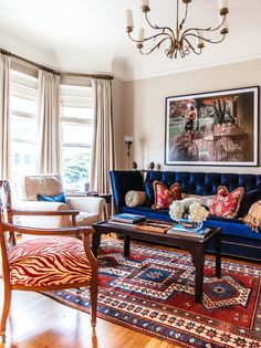 The antique chair was also her grandmother's and was recovered with Cowan & Tout in El Morocco Coral fabric by Colefax and Fowler Marldon. Repainted coffee table from Harrington Galleries in the Mission. Chandelier is from Past Perfect.