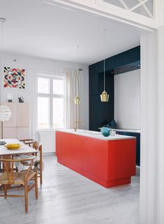 Orange red, tomato red kitchen island and dark teal coloured cabinets paired up . Orange red, tomato red kitchen island and dark teal coloured cabinets paired up against a powder coloured freestanding cabinet, the base is kept white in the apartment.