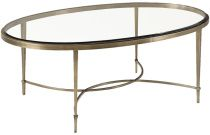 living room coffee table-No. 7854  OVAL COFFEE TABLE    The Oval Cocktail Table features a clear glass, beveled top that sits slightly raised from its surrounding, sleek metal apron. The table is supported by four straight, gently tapered metal legs joined in an interlocking, half-moon stretcher. Baker's signature Antique Brass finish completes the piece.