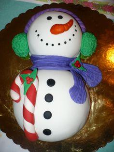 Gracioso Muñeco de Nieve cubierto en fondant, modelado en pastillaje, ponque de almendras, relleno de chocolate amargo con avellanas y conchitas confitadas de naranja.