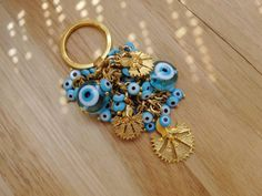 Turquoise glass evil eye beaded keychain with gold plated gillyflower charms.  Large evil eye beads are handmade with murano glass.      ☼ ☼ ☼ ☼ ☼ ☼ ☼