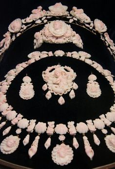 "Coral cameo jewelery set, 1850-1870, Naples, Italy. A complete parure made of rare pink coral, known as ""angel skincoral"" because of its translucent appearance. It is carved with sea horses, mermaids, dolphins, and shells; attaches to a gold framework."