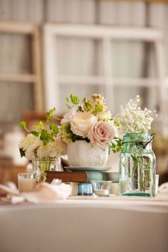 Beautiful flowers in a milk glass vase, mason jars, and a quilt on the table. perfect for an outdoor, low key wedding.