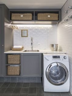 Grey laundry room features gray shaker cabinets paired with a white marble countertop and a white beveled tiled backsplash.