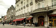 Pedestrians walk by as hungry diners eat at the sidewalk café outside the Grand Hotel in Oslo