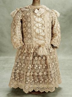 Circa 1880. Child's Dress  of embroidered tulle lace, long coat-style sleeves,scalloped hem, decorated with ivory silk faille panels on the bodice and sleeves that are trimmed with criss-cross cording and velvet/silk tassels, fully-lined. http://Theriaults.com/
