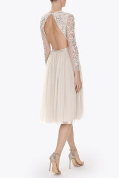 The Floral Border Dress artwork is inspired by Victorian floral lace. The motifs are depicted in shimmering pearlescent embellishment. The delicate tulle fabric allows for the semi-sheer sleeves and these are complimented by the backless feature. The full, layered tulle skirt creates romantic volume and movement. The waist is finished with Needle & Thread's signature grosgrain trim.
