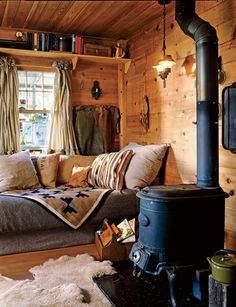 Wooden walls, fireplace, couch with throw pillows and fur space carpets.