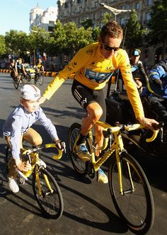 Bradley Wiggins of Great Britain and SKY Procycling celebrates with his son and team-mates on a processional lap after winning the 2012 Tour de France after the twentieth and final stage of the 2012 Tour de France