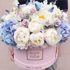 A beautiful floral arrangement of white peonies and blue hydrangeas in a pretty hat box.