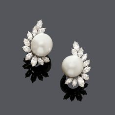 PEARL AND DIAMOND EARCLIPS, BY HARRY WINSTON, Geneva, ca. 1981. Platinum 900, 10% iridium. Each set with 1 fine, bouton-shaped South Sea cultured pearl of ca. 15 mm Ø in a marquise-cut diamond surround of 6.80 ct. Maker's mark TJ for Jaques Tiemey. Findings in gold. Ca. 3,4 x 2,2 cm.
