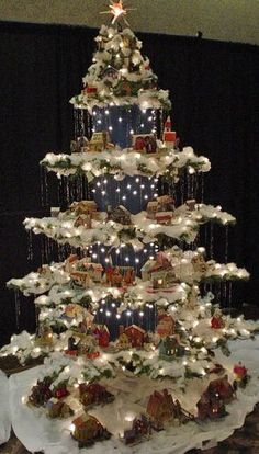 """Beautiful Christmas Display. Created from a regular Christmas tree, this """" antique paper house village"""" tree was made by eliminating every 3rd row and bending the 2 remaining rows  to form a layer. Corrugated blue cardboard with lights punched  through, polyester batting snow, and tinsel icicles help finish the look."""