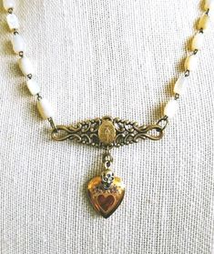 Excited to share the latest addition to my #etsy shop: Pearly gates. A unique vintage assemblage necklace with repurposed mother of pearl rosary beads, gold filled locket, and Miraculous medal. http://etsy.me/2ExPgpB