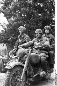 A Feldgendarme with motorbike annd German paratroopers.. France 1944