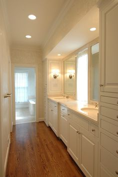 galley style master bathroom. ivory cream damask wallpaper, oak wood floors, white built-in bathroom cabinets with double sinks, marble countertops and walk-in closet.