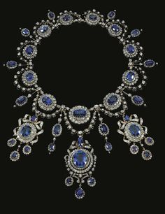 Sapphire and diamond demi-parure,  Mellerio Dits Meller, circa 1870.	 Necklace designed as a chain of 11 clusters, each set with an oval sapphire within a diamond border  supporting  diamond swags & decorated to the  front with 3 detachable drops,  each set with a sapphire within a border of diamonds surmounted by a diamond ribbon bow motif & supporting 3 sapphire & diamond drops. A pair of matching earrings, mounted in silver and gold. French assay marks