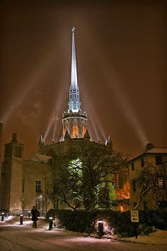 Snow falling on the beautifully lit Hennepin Avenue United Methodist Church in downtown Minneapolis, Minnesota,  English Gothic style and modeled after Ely Cathedral in the UK.  Completed in 1916, the awesome spire stands 28 feet (72 meters) tall and was at the time the second tallest building in Minneapolis - definitely my favorite steeple in town.  Photo by Dan anderson, flickr.com