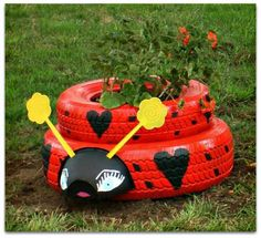 Ladybug planter from two tires, two fly swatters and a bowl.